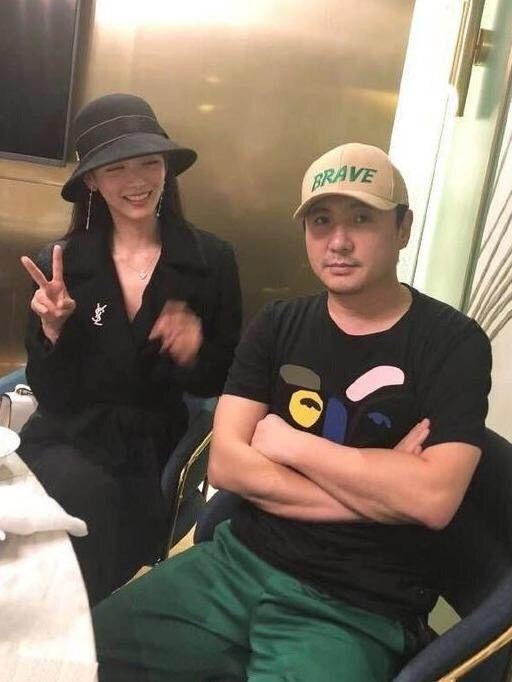 沈腾与网红美女一起吃火锅,双手抱胸很严肃,帽子上绿色字样亮了